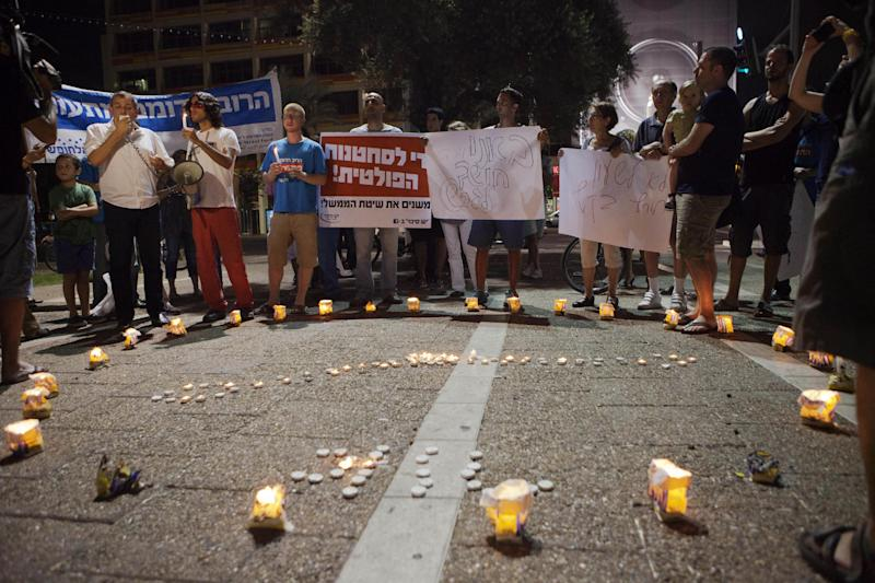 Israelis light candles in the shape of a clock during a protest against the government decision to return to winter clock more than a month ahead of Europe and the U.S. in Tel Aviv, Saturday, Sept 22, 2012. Israel was set to move its clocks back by an hour overnight on Sunday, putting the country on its winter clock more than a month ahead of Europe and the U.S. and adding to the rising anger that many mainstream Israelis feel toward an ultra-Orthodox minority. Yom Kippur, which begins on Tuesday evening, is marked by a sundown-to-sundown fast. Orthodox religious parties, which have always held key swing votes in Israel's political system, are behind the time change, wanting to decrease the number of waking hours for those fasting. (AP Photo/Dan Balilty)