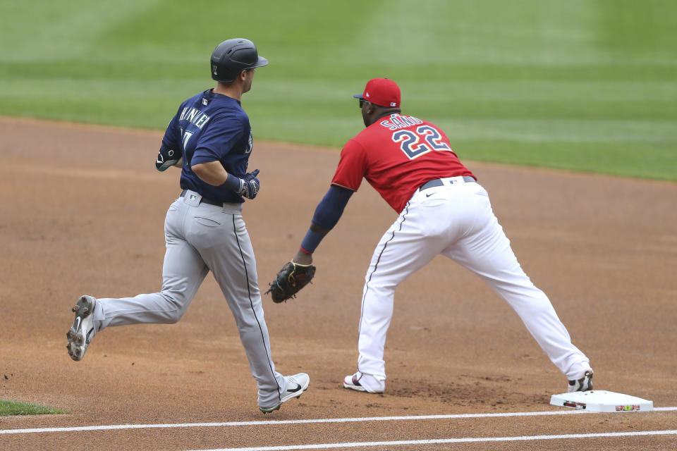 Minnesota Twins' Miguel Sano (22) forces out Seattle Mariners' Mitch Haniger (17) at first after fielding the ball from Twins' Andrelton Simmons (9) during the first inning of a baseball game, Saturday, April 10, 2021, in Minneapolis. (AP Photo/Stacy Bengs)