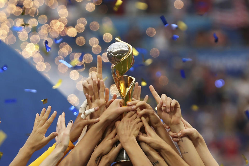FILE - In this July 7, 2019, file photo, the United States players hold the trophy as they celebrate winning the Women's World Cup final soccer match against The Netherlands at the Stade de Lyon in Decines, outside Lyon, France. The 2023 Women's World Cup will be spread across nine cities in Australia and New Zealand. (AP Photo/Francisco Seco, File)
