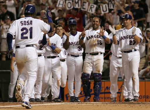 FILE - In this June 20, 2007, file photo, members of the Texas Rangers greet Sammy Sosa (21) as he heads home after connecting for his 600th career home run that came off a pitch from Chicago Cubs' Jason Marquis in the fifth inning of a baseball game in Arlington, Texas. The stadium halfway between Dallas and Fort Worth, first known as The Ballpark in Arlington, is down to its final homestand after more than 2,000 regular season games over 26 seasons. (AP Photo/Tony Gutierrez, File)