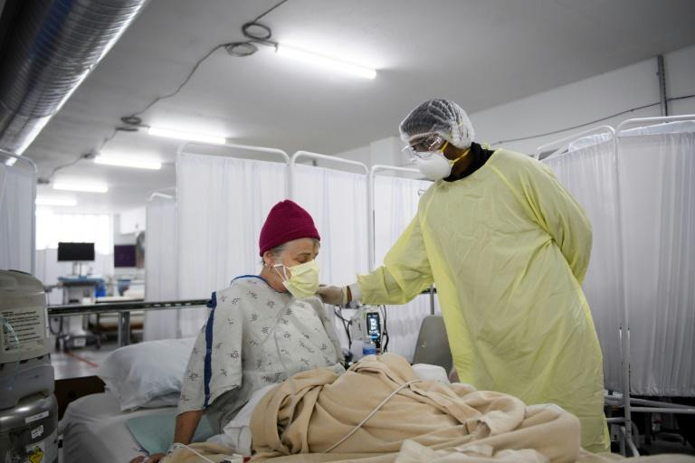 Dr. Bijay Sah examines a patient with Covid-19 at an indoor parking lot converted into a care unit in Reno, Nevada