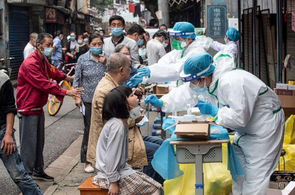 PHOTO: This file photo taken on May 15, 2020, shows medical workers taking swab samples from residents to be tested for COVID-19 in a street in Wuhan in China's central Hubei province. (Str/AFP via Getty Images)