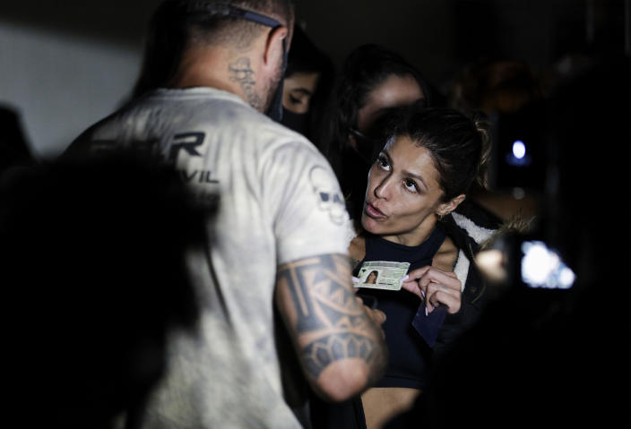 A woman presents her identification as police break up a social gathering during an operation against illegal and clandestine gatherings that authorities believe are partly responsible for fueling the spread of COVID-19, at a party hall in Sao Paulo, Brazil, early Saturday, April 17, 2021. (AP Photo/Marcelo Chello)