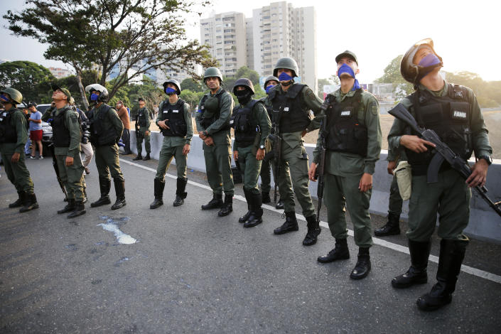 FILE - In this April 30, 2019 file photo, troops loyal to Venezuela's opposition leader and self proclaimed President Juan Guaido, stand outside La Carlota air base in Caracas, Venezuela. (AP Photo/Ariana Cubillos, File)