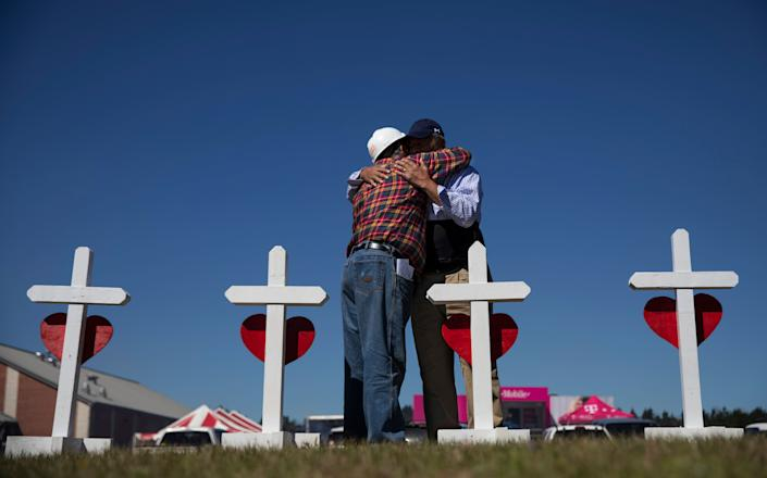 Rev. Arthur Thomas, right, of Mt. Nebo Baptist Church, right, is embraced by Greg Zanis who built a cross for each victim of the tornado and placed them as a makeshift memorial in Beauregard, Ala., Wednesday, March 6, 2019. Thomas said several of the dead were members of his congregation. (AP Photo/David Goldman)