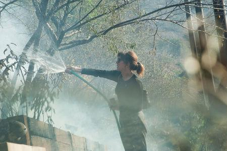 Elizabeth Rawjee sprays water from a garden hose onto hotspots left by the Skirball fire in her backyard on the west side of Los Angeles, California, U.S., December 6, 2017. REUTERS/Andrew Cullen