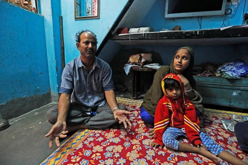 Fareeda and her husband Abdul Hanif sit with their four-year-old daughter inside their house in New Delhi