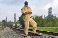 """Activist Hilton Kelley poses along the railroad tracks that divide East and West Port Arthur Monday, March 23, 2020, in Port Arthur, Texas. """"Now we may not drop dead that day,"""" Kelley said of the environmental protection rollbacks, and the communities surrounding the refineries and plants. """"But when you're inundated day after day...we're dead. We're dead."""" (AP Photo/David J. Phillip)"""