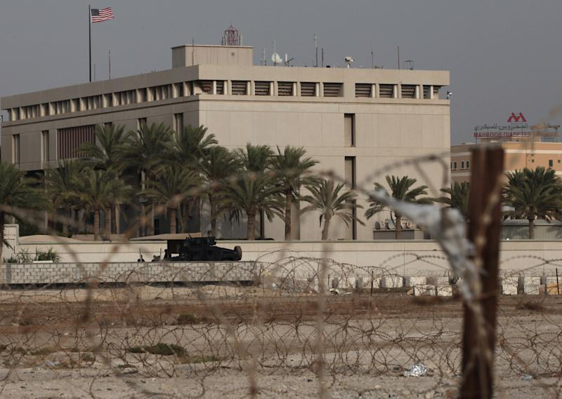 A Bahraini armored personnel vehicle and personnel reinforce U.S. Embassy security just outside of a gate to the building, surrounded in barbed wire, in Manama, Bahrain, on Sunday, Aug. 4, 2013. Security forces close access roads, put up extra blast walls and beef up patrols near some of the 21 U.S. diplomatic missions in the Muslim world that Washington ordered closed for the weekend over a ``significant threat'' of an al-Qaida attack. (AP Photo/Hasan Jamali)