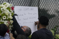 Miami Heat forward Udonis Haslem writes a message on the wall as flowers he brought are affixed beside it, at a makeshift memorial to the people who were killed and the scores who remain missing, nearly a week after the partial collapse of the Champlain Towers South condo building, Wednesday, June 30, 2021, in Surfside, Fla. (AP Photo/Gerald Herbert)