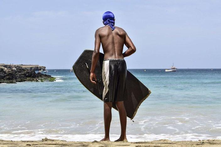 A young man looks to the sea as he holds his bodyboard.