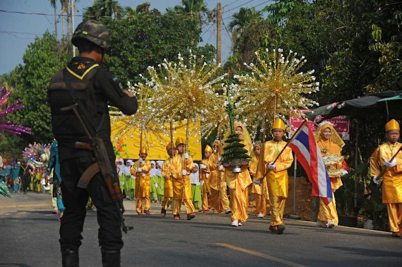 A Thai soldier stands guard as Muslim schoolchildren participate in the opening parade of a festival in the Rangae district of Thailand's restive southern Narathiwat province on April 16, 2016