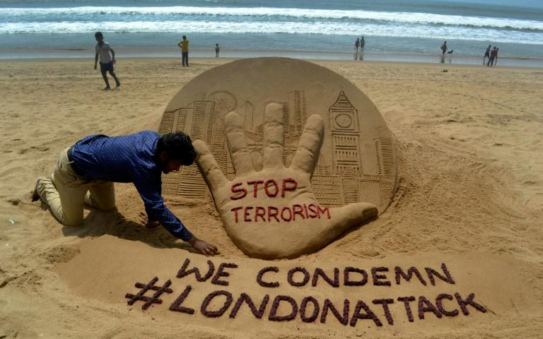 Indian sand artist Sudarsan Pattnaik creates a sculpture on Puri Beach on the Bay of Bengal the day after the London attack