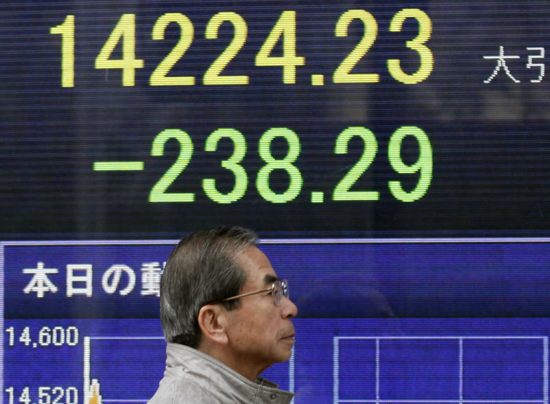 A man walks by an electronic stock board of a securities firm in Tokyo, Thursday, March 20, 2014. Asian stocks inched down Thursday after comments from the new head of the Federal Reserve suggested U.S. interest rates could rise sooner than financial markets were anticipating. (AP Photo/Koji Sasahara)
