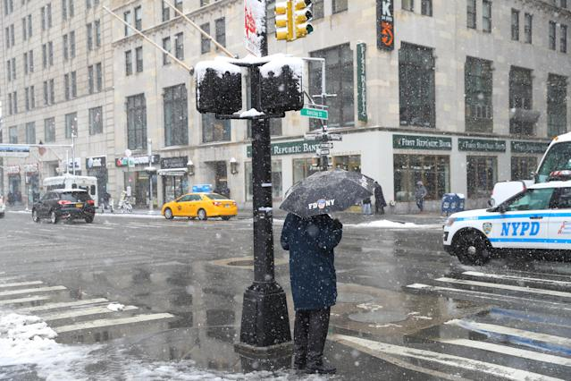 <p>A pedestrian carrying an umbrella waits to cross Broadway in lower Manhattan in New York City as a spring storm hit the Northeast on Wednesday, March 21, 2018. (Photo: Gordon Donovan/Yahoo News) </p>
