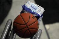Alcohol wipes sit next to a basketball that will be used in an upcoming NCAA college basketball game between San Francisco and Virginia, Friday, Nov. 27, 2020, in Uncasville, Conn. (AP Photo/Jessica Hill)