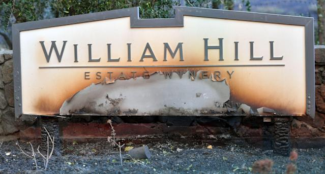 <p>The William Hill Estate winery sign is seen partially burnt in Napa, California on Oct., 9, 2017, as multiple wind-driven fires continue to whip through the region. (Photo: Josh Edelson/AFP/Getty Images) </p>