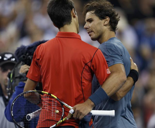 Rafael Nadal of Spain is congratulated by Novak Djokovic of Serbia (L) after his victory in their men's final match at the U.S. Open tennis championships in New York, September 9, 2013. REUTERS/Eduardo Munoz (UNITED STATES - Tags: SPORT TENNIS)