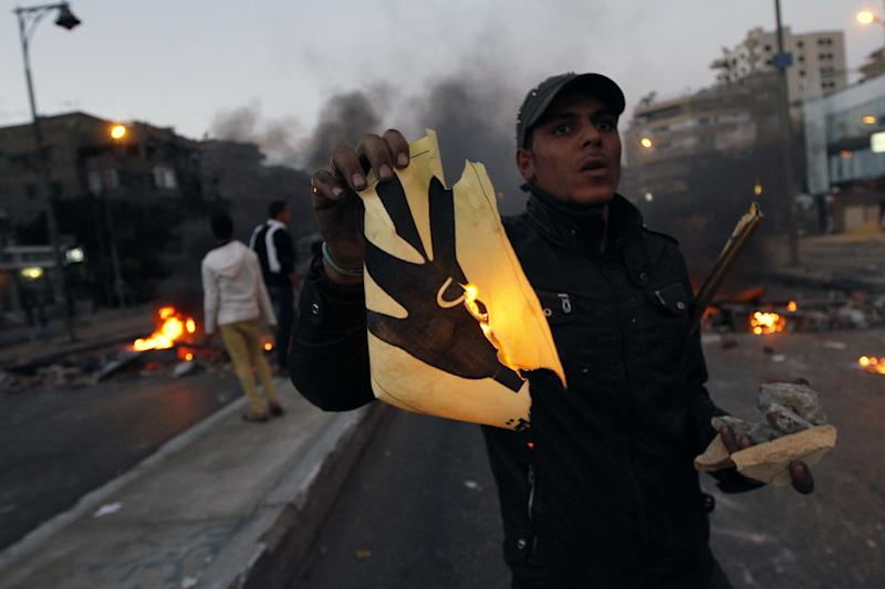 A protester against the Muslim Brotherhood holds up a burning poster of four raised fingers during clashes with supporters of the Muslim Brotherhood in the Nasr City district in Cairo, Egypt, Friday, Nov. 22, 2013. The posters of four raised fingers became a symbol for supporters of ousted Islamist President Mohammed Morsi. Clashes erupted Friday as thousands of supporters of the Muslim Brotherhood around Egypt held protests marking the passage of 100 days since the start of a bloody crackdown against them in the wake of the ouster of the Islamist president. The violence left at least two dead including a 10-year-old boy. (AP Photo/El-Shorouk newspaper, Sabry Khaled) EGYPT OUT