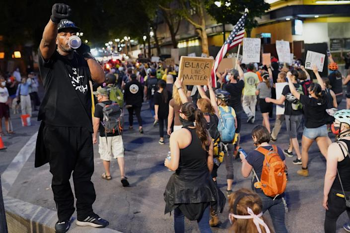 Protesters marched past the Mark O. Hatfield U.S. Courthouse in Portland, Ore., on Thursday, when federal officers began a phased withdrawal from the city. (Photo: Nathan Howard/Getty Images)