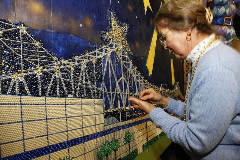 """This Jan. 14, 2013 photo shows volunteer Gail Dusenberry of Clyde, North Carolina working on Artist Stephan Wanger""""s bead mosaic """"Paragons of New Orleans"""" at Mardi Gras World in New Orleans. Super Bowl takes place in New Orleans on Feb. 3 and Mardi Gras falls nine days later on Feb. 12. With both events so close together, New Orleans is bracing for a massive celebration and record crowds. (AP Photo/Bill Haber)"""