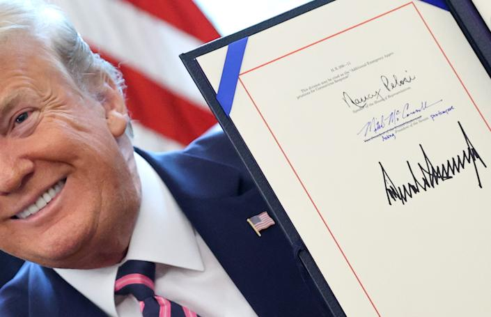 U.S. President Donald Trump holds the Paycheck Protection Program and Health Care Enhancement Act after signing the coronavirus disease (COVID-19) relief bill in the Oval Office at the White House in Washington, U.S. April 24, 2020.  (Jonathan Ernst/Reuters)