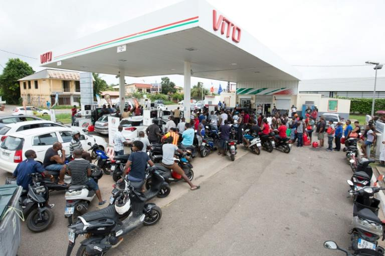 People queue with vehicles and jerrycans after a tank truck was able to resupply an out-of-fuel petrol station in Cayenne, French Guiana's capital