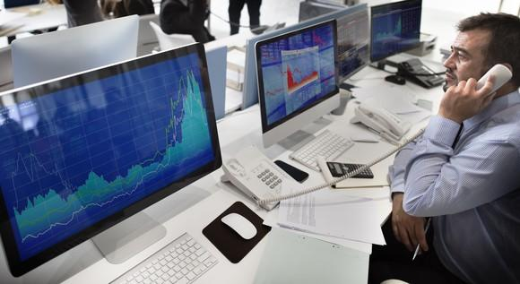 An equities trader on the phone while in front of his computer.