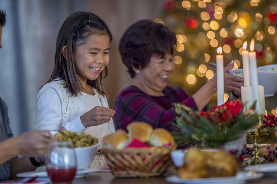 FILE PHOTO: An Asian family is indoors having dinner together on Christmas day. There is lots of traditional Christmas food on the table. The grandmother and granddaughter are helping themselves to rolls and mashed potatoes. (Source: Getty Creative)