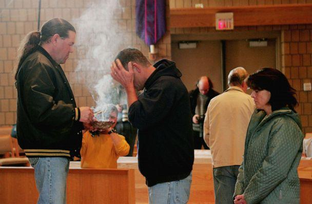 PHOTO: Robert Cook from the Red Lake Indian Reservation, performs a traditional ceremony at St. Phillip Church during a memorial service to mourn the victims killed at Red Lake High School, March 23, 2005, in Bemidji, Minn. (Scott Olson/Getty Images)