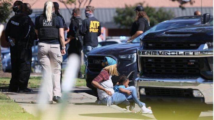A woman and child rest outside the supermarket crime scene