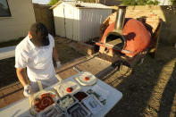 Chef Jose Hernandez preps several pizzas at a makeshift backyard pizza kitchen on April 3, 2021, in Scottsdale, Ariz. Beaten down by the pandemic, some laid-off or idle restaurant workers have pivoted to dishing out food from home. (AP Photo/Ross D. Franklin)