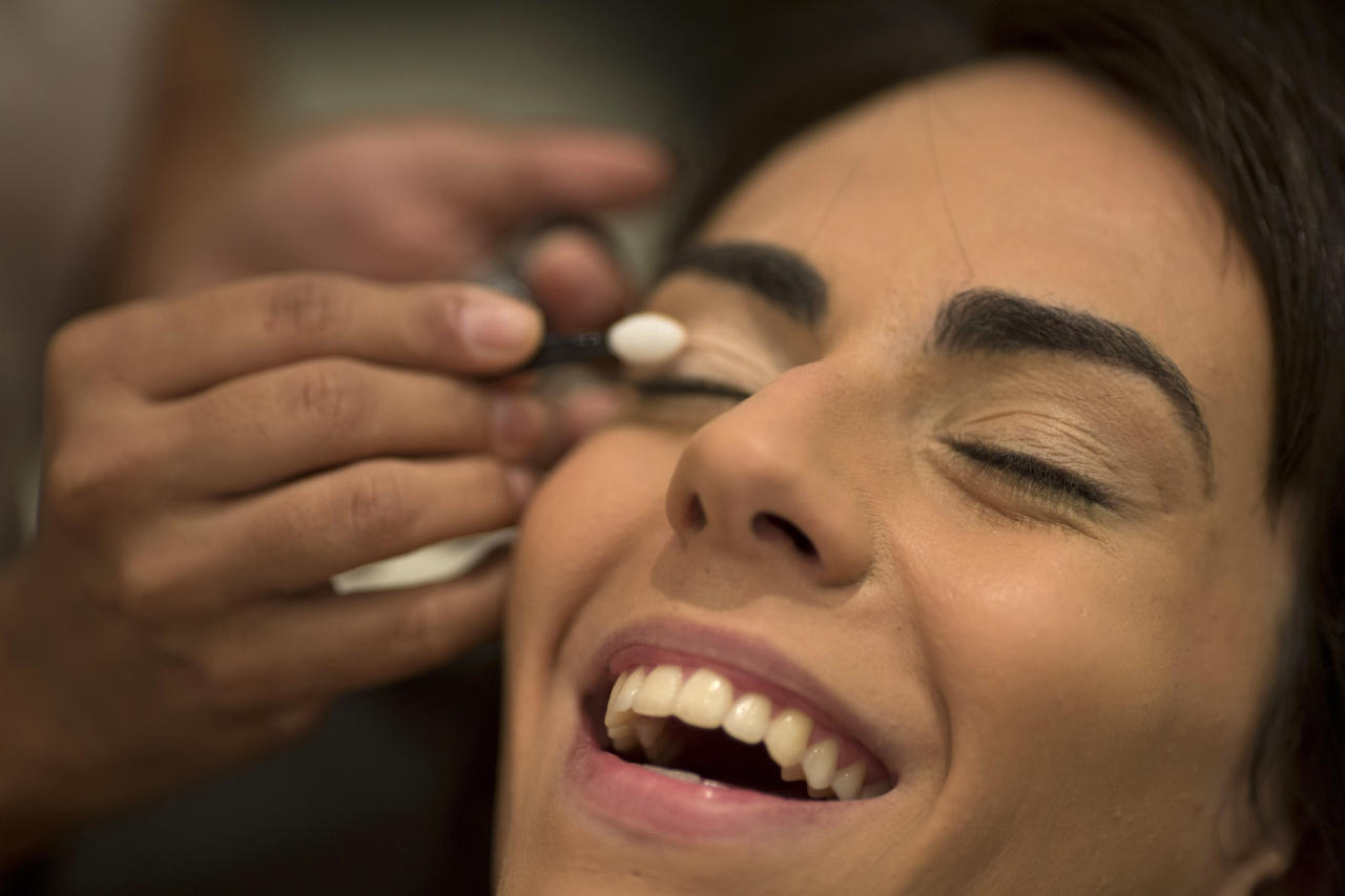 In this Dec. 4, 2012 photo, Brazilian transgender model Felipa Tavares has her makeup applied in preparation for a photo session in Rio de Janeiro, Brazil. The 6-foot-tall Tavares is among Brazil's small but growing ranks of transgender models _ leggy, high-cheekboned sirens who were born men and are causing a splash here as well as in Paris and other international fashion capitals. (AP Photo/Felipe Dana)