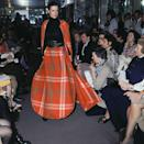 <p>Cardin's ready-to-wear collection showcased looks such as this oversized plaid skirt and matching cape, styled with a high-waisted belt.</p>
