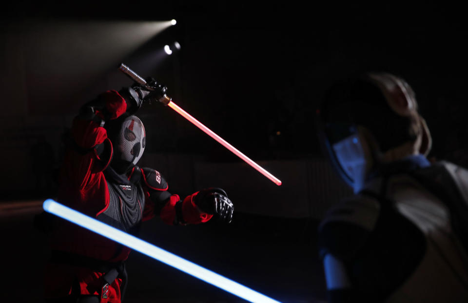 In this Sunday, Feb. 10, 2019, photo, Julien Esprit, left, competes with Jean Baptiste Marchetti-Waternaux during the national lightsabers tournament in Beaumont-sur-Oise, north of Paris. In France, lightsaber fighting is an official sport, recognized as such by the French Fencing Federation. The sport's practitioners, many but not all of the fans of 'Stars Wars,' have had to build the discipline's competition rules almost from scratch. (AP Photo/Christophe Ena)