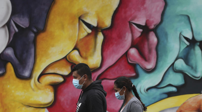 Pedestrians, wearing protective face masks as a precaution against the spread of the new coronavirus, walk past a mural in Quito, Ecuador, Saturday, March 28, 2020. The government has declared a health emergency, enacting a curfew and restricting movement to only those who provide basic services. (AP Photo/Dolores Ochoa)