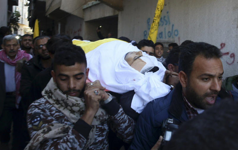 Mourners carry the body of Tamer Arafat, 23, during his funeral in front of his family house in Rafah refugee camp, southern Gaza Strip, Saturday, March 9, 2019. Arafat was shot in the head by Israeli troops during Friday protest at the Gaza Strip's border with Israel the Palestinian health ministry said. (AP Photo/Adel Hana)