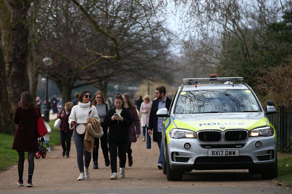 <p>People walk past a police car parked at Hyde Park</p> (Getty Images)