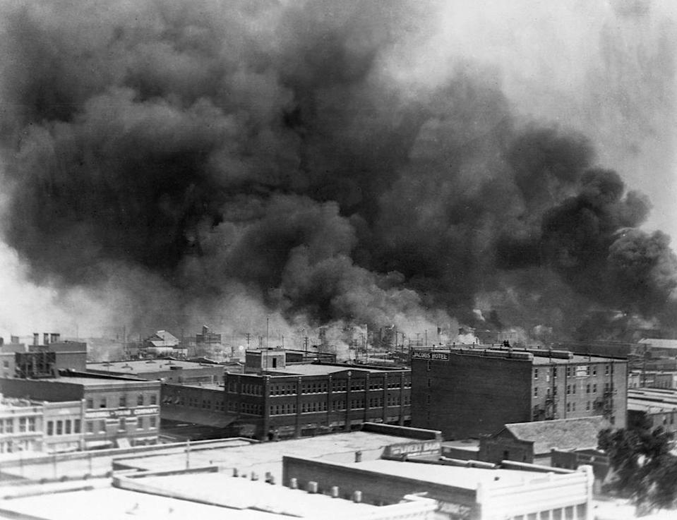 Black smoke billows from fires during the Tulsa Race Massacre of 1921,  in the Greenwood District, Tulsa, Oklahoma, US, June 1921. / Credit: Corbis via Getty