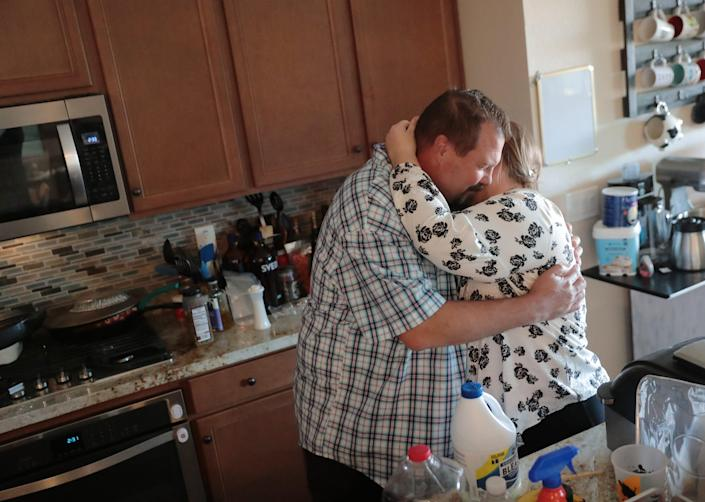 George Adair hugs his wife, Catherine, inside their Buckeye home Feb. 14, 2021. George's mother, Phyllis, was a flight attendant for American Airlines and died Feb. 2 from COVID-19.