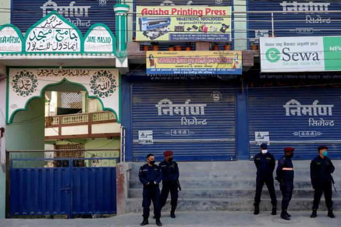 Nepalese police officers stand guard in front of a mosque as locals protest against Indonesians taking shelter at the mosque, amid fear of outsiders spreading coronavirus disease (COVID-19), at Jame Masjid in Imadol, Lalitpur