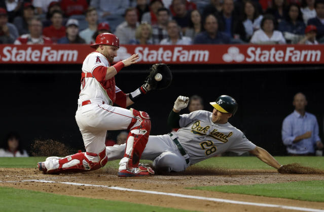 Oakland Athletics' Matt Olson, right, scores past Los Angeles Angels catcher Jonathan Lucroy on a sacrifice fly by Stephen Piscotty during the third inning of a baseball game Tuesday, June 4, 2019, in Anaheim, Calif. (AP Photo/Marcio Jose Sanchez)