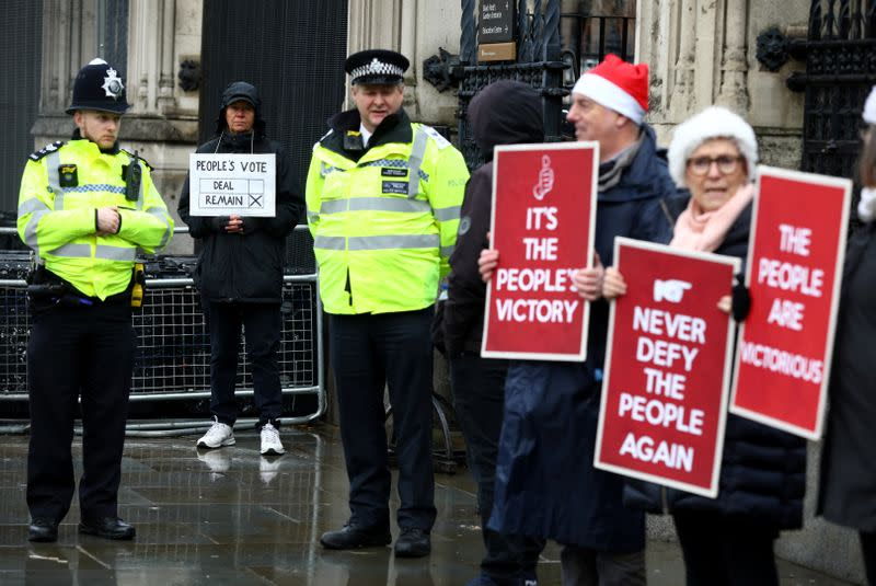Protesters hold placards outside the Houses of Parliament in London