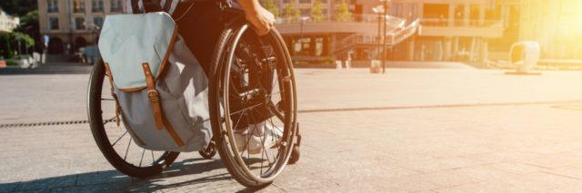 Person in a manual wheelchair outdoors.