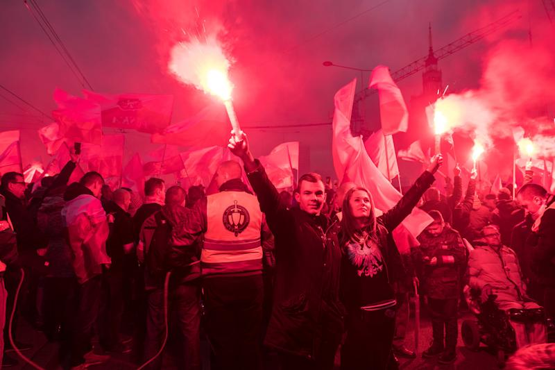 A couple holds flares as thousands gather for the annual march for Poland's Independence Day. The annual event marks the restoration of the country'ssovereignty and is celebrated on Nov. 11. (SOPA Images via Getty Images)