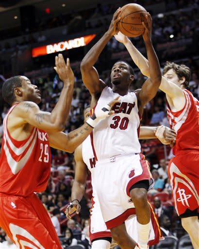 Miami Heat guard Norris Cole (30) shoots against Houston Rockets center Marcus Camby (29) and guard Goran Dragic during the first half of an NBA basketball game, Sunday, April 22, 2012, in Miami. (AP Photo/Wilfredo Lee)