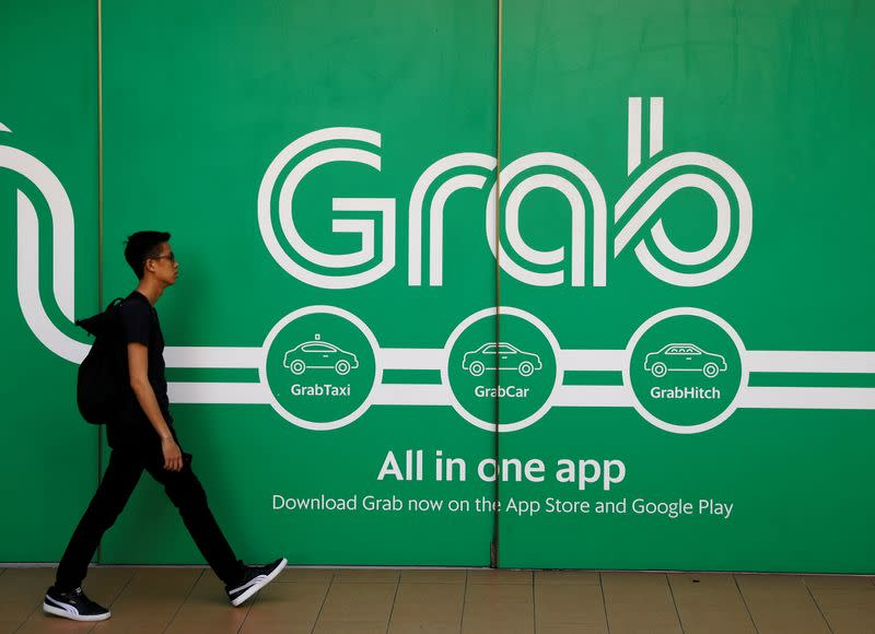 FILE PHOTO: A man walks past a Grab office in Singapore