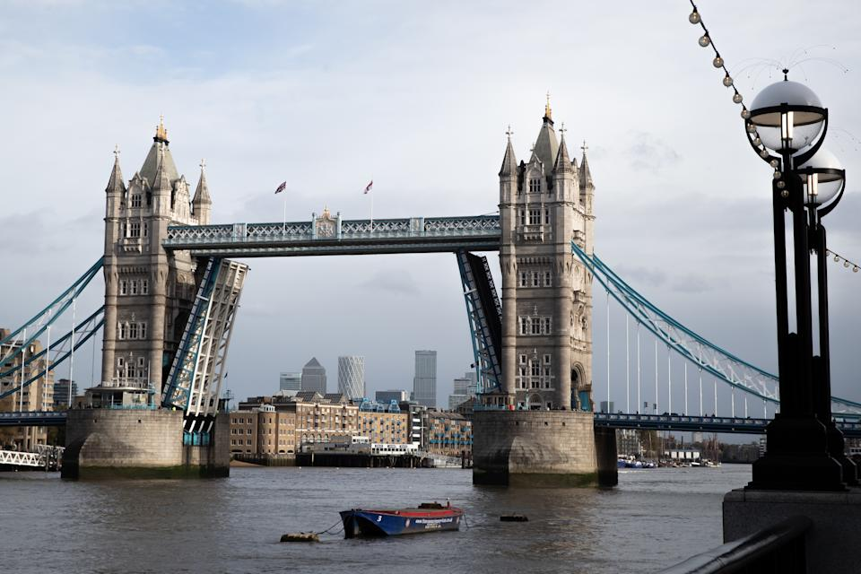 A general view of an open Tower Bridge with the skyline of Canary Wharf, London.