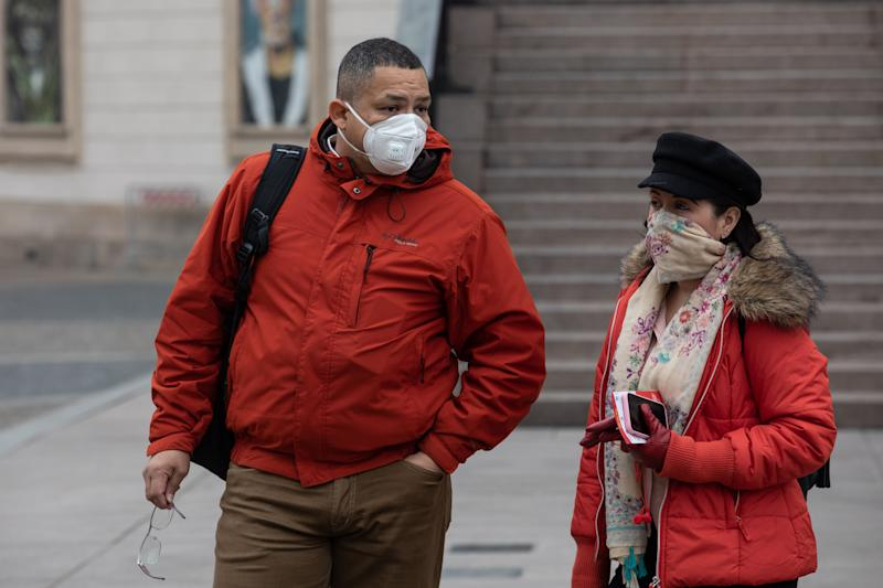 MILAN, ITALY - FEBRUARY 25: Two people, both wearing a respiratory mask, stand in Piazza del Duomo on February 25, 2020 in Milan, Italy. Italy is the last country to be hit hard by the virus with 7 dead and more than 283 infected as of today. The spread marks Europe's biggest outbreak, prompting the Italian Government to issue draconian safety measures. (Photo by Emanuele Cremaschi/Getty Images)