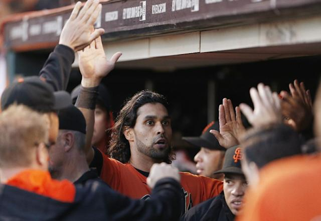 San Francisco Giants' Angel Pagan is congratulated after scoring a run during the third inning of a baseball game against the Colorado Rockies in San Francisco, Friday, June 13, 2014. (AP Photo/Beck Diefenbach)